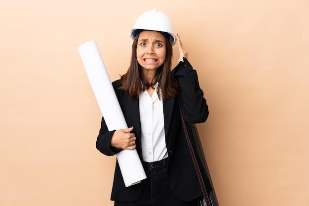 Młoda kobieta architekta posiadających plany robi nerwowy gest