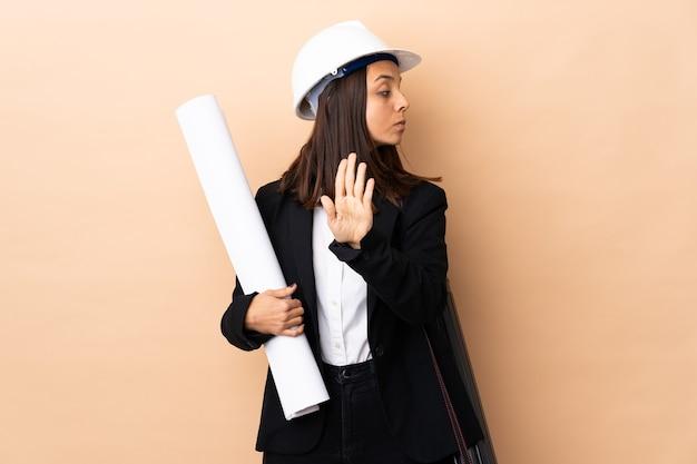 Młoda kobieta architekta trzymając plany na odizolowanej ścianie, co gest zatrzymania i rozczarowany
