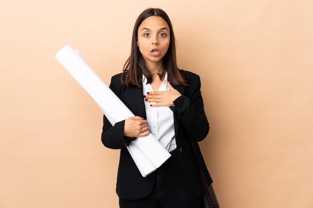 Młoda kobieta architekta trzymająca plany na odizolowanej ścianie zaskoczona i zszokowana, patrząc w prawo