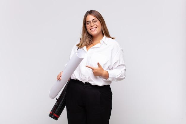 Młoda kobieta architekta uśmiecha się radośnie, czuje się szczęśliwy i wskazuje na bok i do góry, pokazując obiekt w przestrzeni kopii