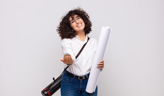 Młoda kobieta architekta uśmiecha się radośnie z przyjaznym, pewnym siebie, pozytywnym spojrzeniem, oferuje i pokazuje przedmiot lub koncepcję