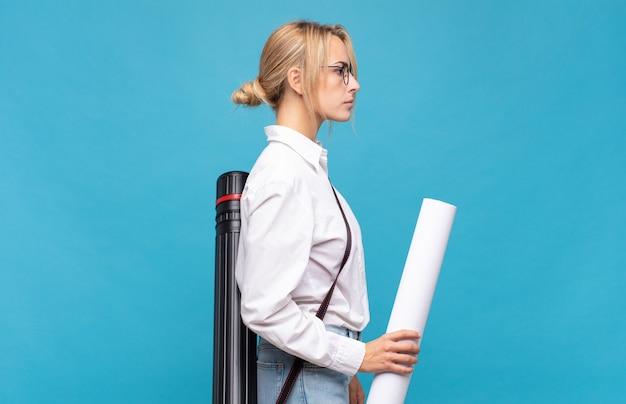 Młoda kobieta architekta w widoku profilu chce skopiować przestrzeń do przodu, myśląc, wyobrażając sobie lub marzyć