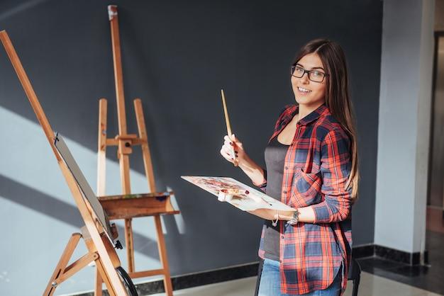 Młoda kobieta artysta maluje obrazek