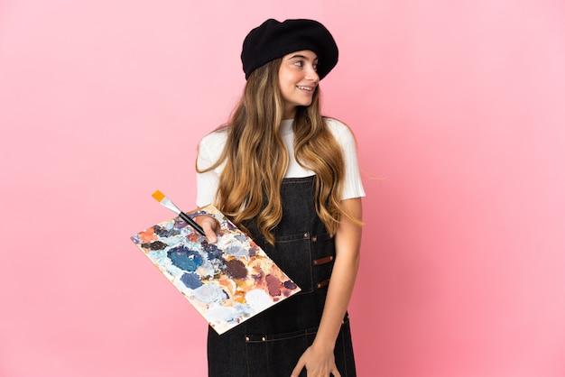 Młoda kobieta artysta trzyma paletę na białym tle na różowej ścianie, patrząc z boku i uśmiechnięty