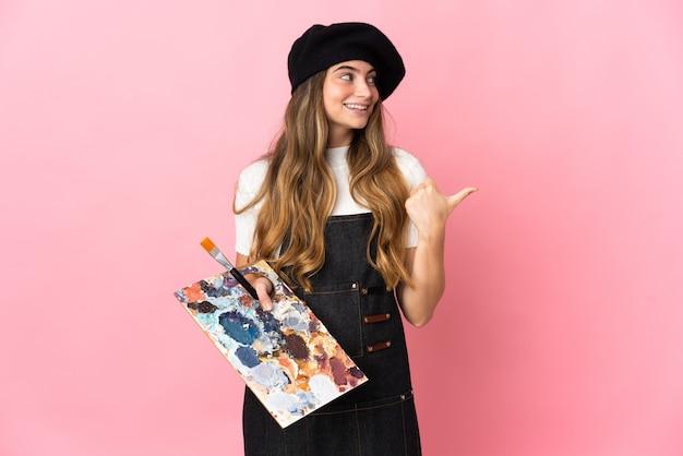 Młoda kobieta artysta trzyma paletę na białym tle na różowej ścianie, wskazując w bok, aby przedstawić produkt