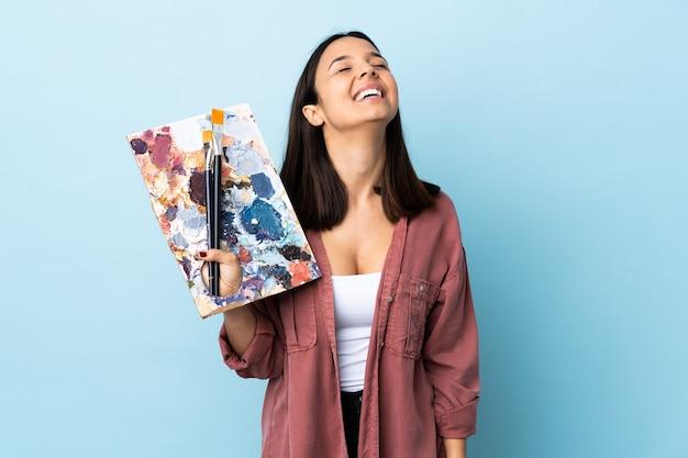 Młoda kobieta artysta trzyma paletę na białym tle niebieskim tle, śmiejąc się.
