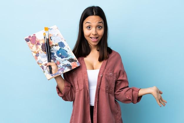 Młoda kobieta artysta trzyma paletę na odosobnionej niebieskiej ścianie szczęśliwa i uśmiechnięta.