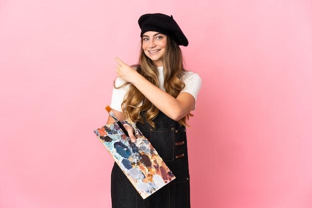 Młoda kobieta artysta trzyma paletę na różowym tle, wskazując na bok, aby przedstawić produkt