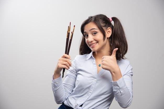 Młoda kobieta artysta z fryzurą kucyk, dając kciuki do góry. wysokiej jakości ilustracja