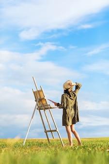 Młoda kobieta artysta ze sztalugami na zewnątrz w słoneczny letni wieczór