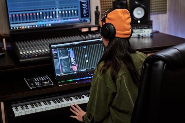 Młoda kobieta artystka patrząca skupiona podczas grania na syntezatorze klawiaturowym siedząca w nagraniu