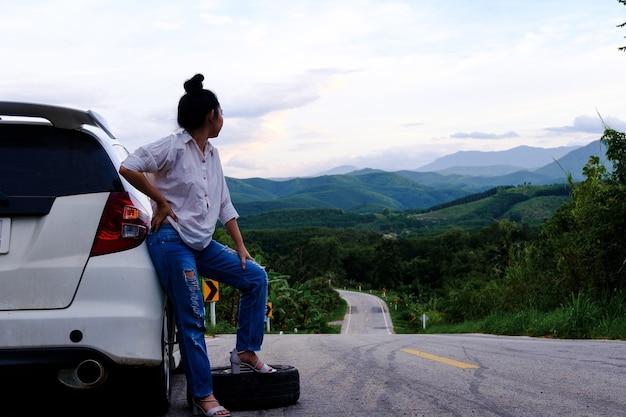 Młoda kobieta asea szlifuje w pobliżu samochodu za wezwanie pomocy na drodze publicznej w lesie w backgrou góry i nieba