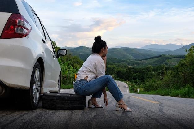 Młoda kobieta asea w pobliżu samochodu za wezwanie pomocy na drodze publicznej w lesie w górach