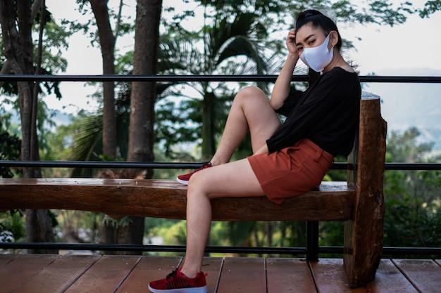 Młoda kobieta asia siedzi na drewnianej ławce i nakłada maskę na twarz w celu ochrony przed unoszącymi się w powietrzu chorobami układu oddechowego, takimi jak grypa i smog w parku, koncepcja bezpieczeństwa kobiet dotycząca infekcji wirusowych