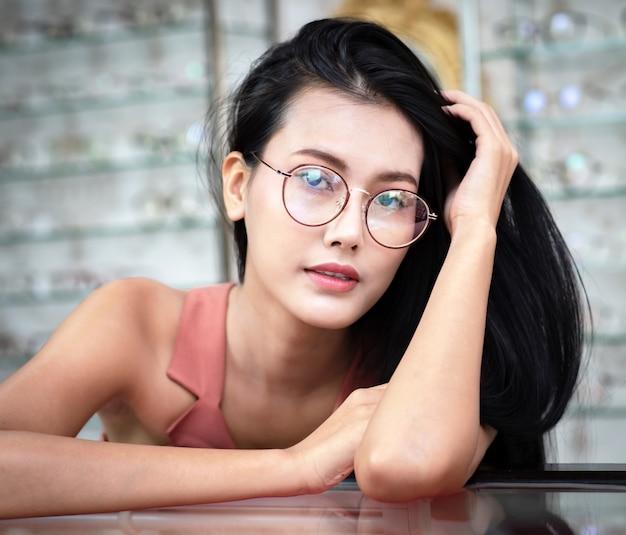 Młoda kobieta asia wybiera okulary w sklepie optyka.