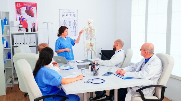Młoda kobieta asystent wskazując na szkielet przed chirurgów w sali konferencyjnej. ekspert kliniczny terapeuta rozmawiający z kolegami o chorobie, specjalista od medycyny