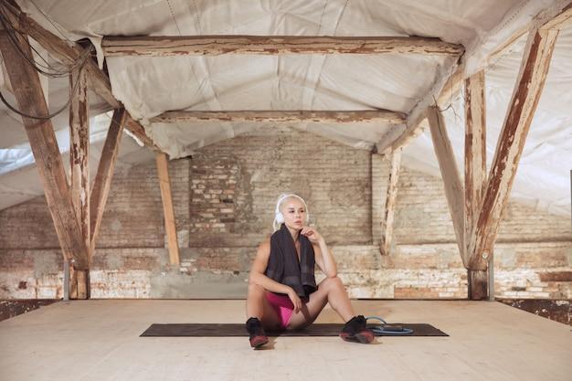 Młoda kobieta atletyczna w białych słuchawkach pracuje, słuchając muzyki na opuszczonej budowie. odpoczynek po treningu. pojęcie zdrowego stylu życia, sportu, aktywności, utraty wagi.