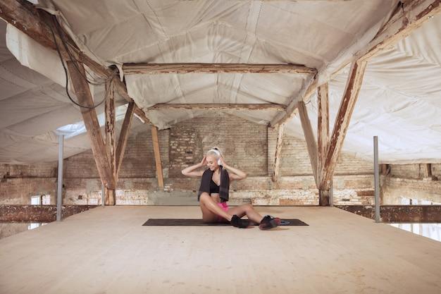 Młoda kobieta atletyczna w białych słuchawkach pracuje, słuchając muzyki na opuszczonej budowie