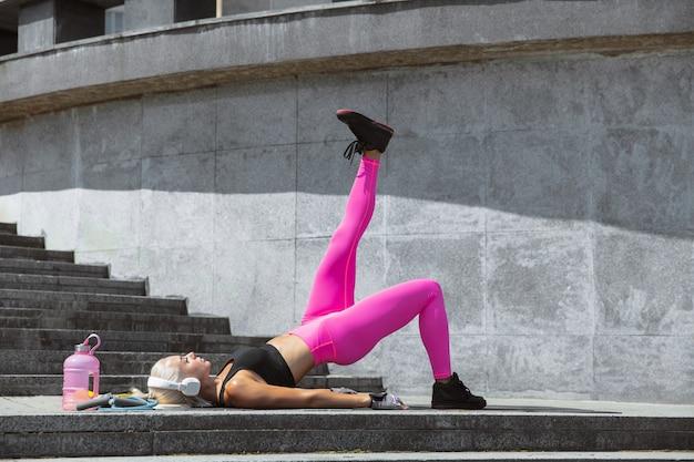 Młoda kobieta atletyczna w białych słuchawkach szkolenia, słuchanie muzyki na ulicy na świeżym powietrzu. wyciąganie górnej i dolnej części ciała. pojęcie zdrowego stylu życia, sportu, aktywności, utraty wagi.