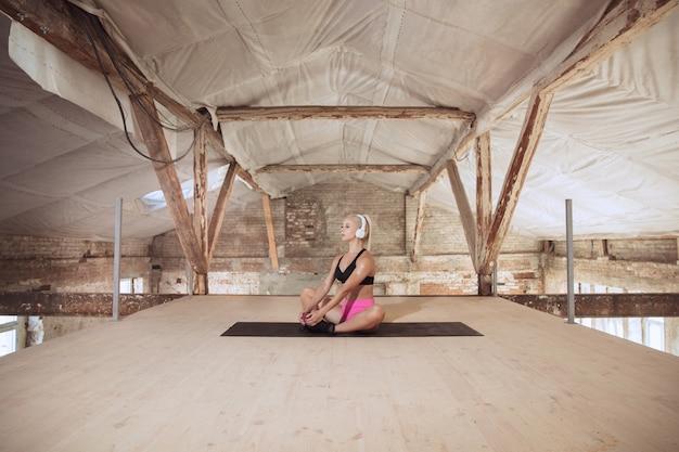 Młoda kobieta atletyczna w koszuli i białych słuchawkach pracuje, słuchając muzyki na opuszczonej budowie