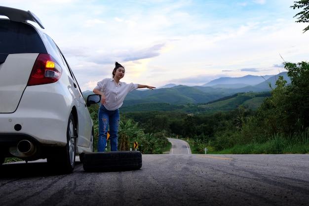 Młoda kobieta autostopem na drodze na drodze publicznej w obszarze leśnym na tle góry i nieba