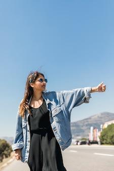 Młoda kobieta autostopem na słonecznej drodze