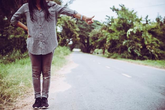Młoda kobieta autostopem wzdłuż drogi.