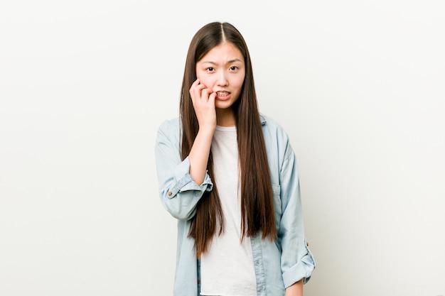 Młoda kobieta azjatycka obgryzająca paznokcie, nerwowa i bardzo niespokojna.