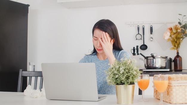 Młoda kobieta azjatyckich biznesowych ewidencji dochodów i wydatków w domu. pani zmartwiona, poważna, stresująca podczas korzystania z rekordowego budżetu laptopa, podatku, dokumentu finansowego pracującego w nowoczesnej kuchni w domu.