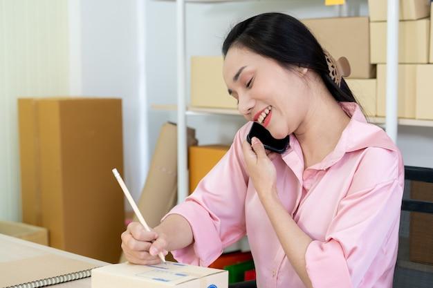Młoda kobieta azjatyckich biznesowych pakowania skrzynek pocztowych, które mają być wysłane do klientów. koncepcja zakupów online e-commerce. doświadczenie sprzedawcy online pakującego paczki klientów do wysyłki.