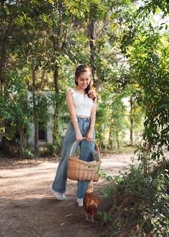 Młoda kobieta azjatyckich, ciesząc się z trzymając kosz z rattanu i kury w ogrodzie w słoneczny