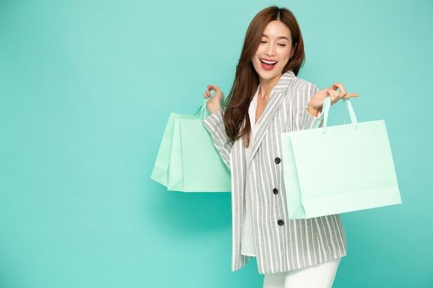 Młoda kobieta azjatyckich gospodarstwa jasnozielone torby na zakupy na białym tle na zielonym tle