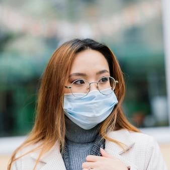 Młoda kobieta azjatyckich noszenie maski stojącej na krajowej ulicy