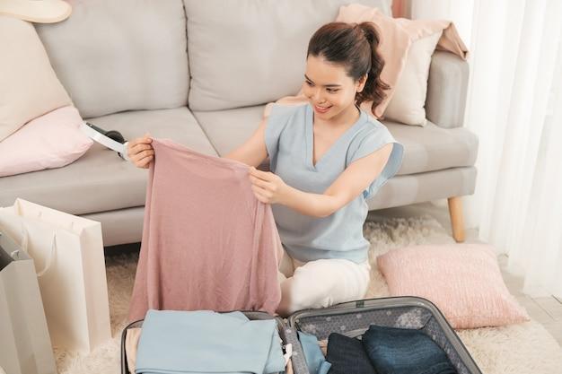 Młoda kobieta azjatyckich pakowania ubrań do torby podróżnej - koncepcja bagażu i osób