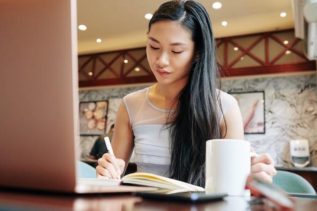 Młoda kobieta azjatyckich planowanie napełniania podczas picia porannej kawy w kawiarni