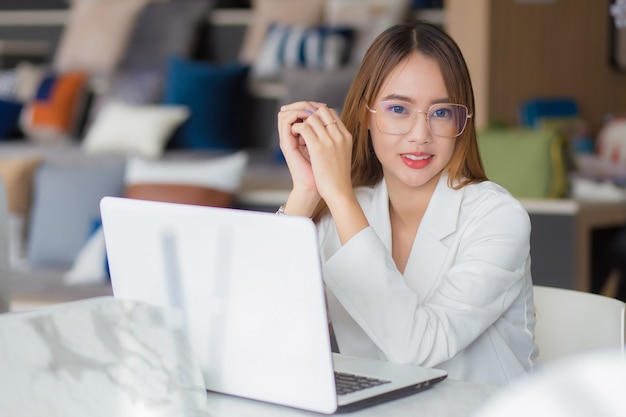 Młoda kobieta azjatyckich profesjonalnych firm w okularach pracuje w przestrzeni coworkingowej z laptopem papierkowa robota (koncepcja kobiety biznesu).