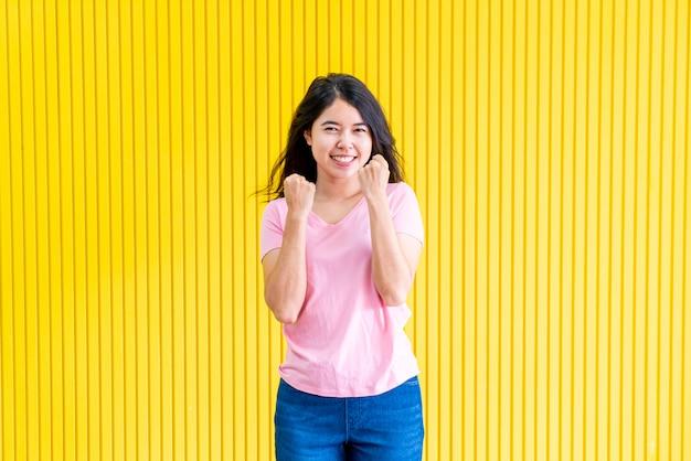 Młoda kobieta azjatyckich szczęścia stojąc na żółtej ścianie
