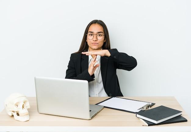 Młoda kobieta azjatyckich traumatologa na białym tle na białej ścianie pokazuje gest limitu czasu.