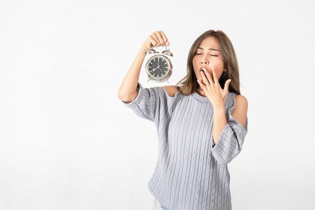 Młoda kobieta azjatyckich trzyma budzik