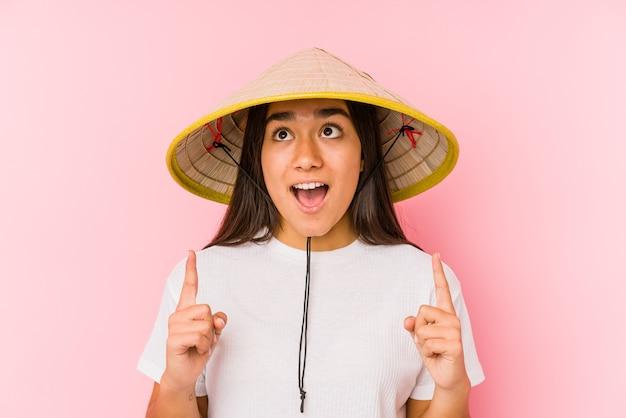 Młoda kobieta azjatyckich ubrana w wietnamski kapelusz izolowanych młoda kobieta azjatyckich ubrana w wietnamski hatpointing górę z otwartymi ustami.