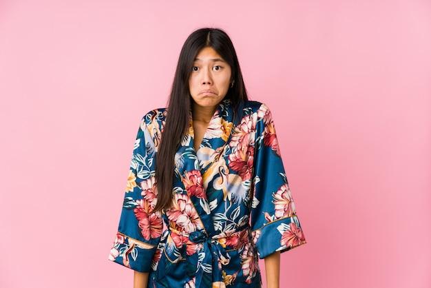 Młoda kobieta azjatyckich w piżamie kimono wzrusza ramionami i zmieszane otwarte oczy.