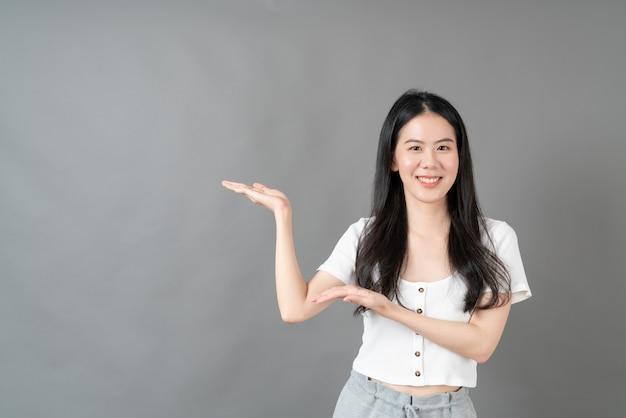Młoda kobieta azjatyckich z uśmiechniętą twarz i ręką, przedstawiając po stronie szarej ściany