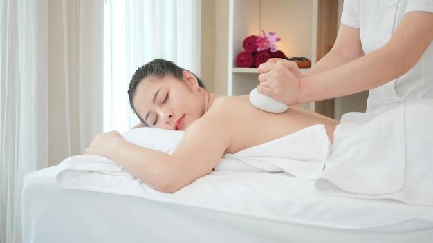 Młoda kobieta azji coraz masaż spa tajski masaż ziołowy piłka gorący kompres w salonie piękności. masaż relaksacyjny dla zdrowia