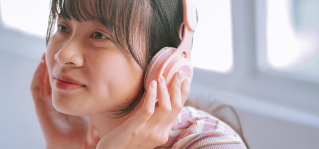 Młoda kobieta azji do słuchania muzyki za pomocą słuchawek bezprzewodowych