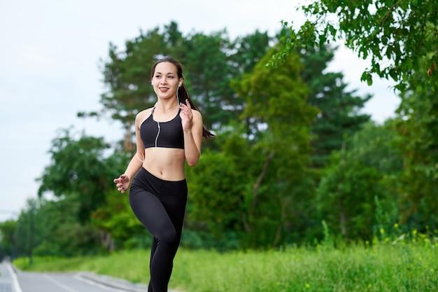 Młoda kobieta azji fitness działa na leśnym szlaku.