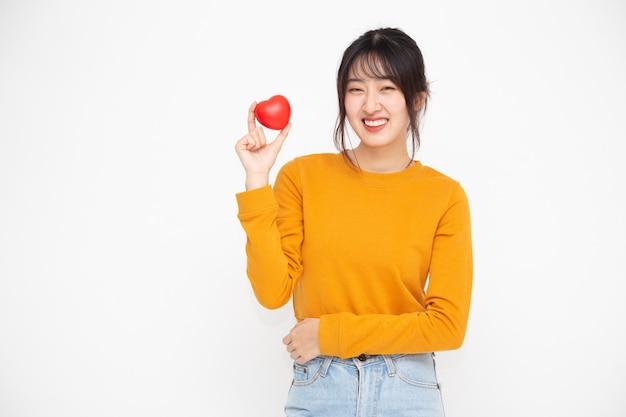 Młoda kobieta azji gospodarstwa czerwone serce miłość na białym tle na białej ścianie