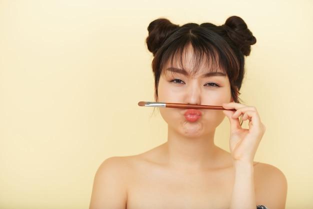 Młoda kobieta azji, krzywiąc się z pędzlem do powiek między ustami i nosem