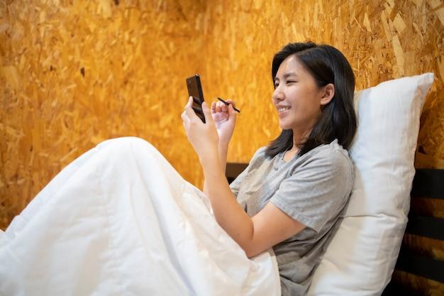 Młoda kobieta azji leżącej na telefonie komórkowym