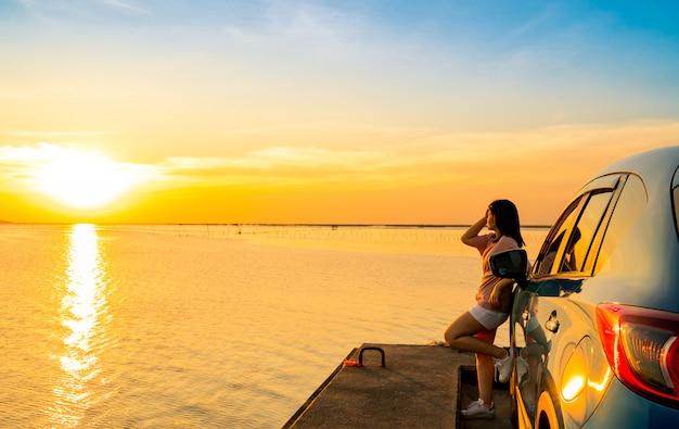 Młoda kobieta azji nosić koszulkę, krótkie spodnie stoją pochylony niebieski kompaktowy samochód sportowy suv nad morzem o zachodzie słońca
