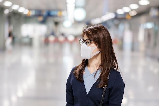Młoda kobieta azji nosząca maskę ochronną przed nowatorskim koronawirusem lub chorobą wirusową corona (covid-19) na lotnisku